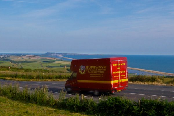 Sureways Weymouth removals van driving down Abbotsbury Hill with St Catherines chapel and the Isle of Portland in the background